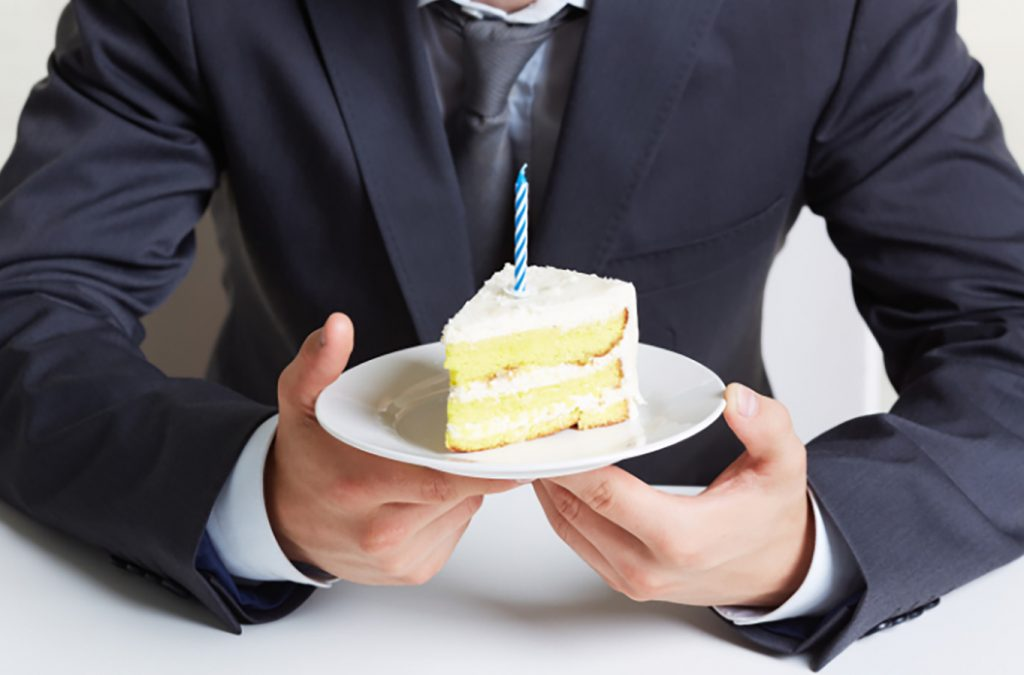 Boss in a suit holding a piece of vanilla birthday cake